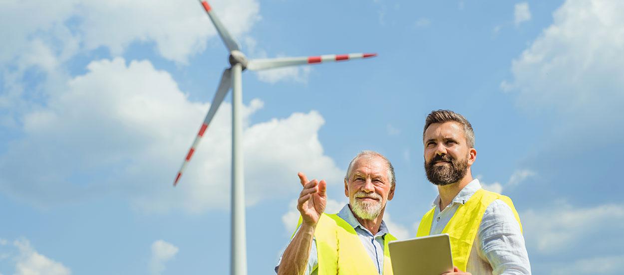 Ingenieros discutiendo sobre la organización de un parque eólico teniendo en cuenta los riesgos de la transición energética