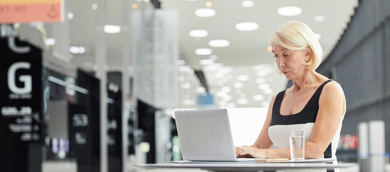 Mujer con pelo rubio y corto sentada en una mesa y escribiendo en su pórtatil en el hall de una oficina